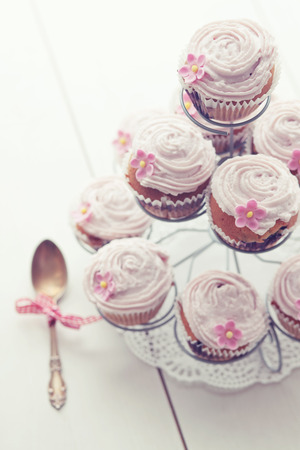 pink cake: Pink cupcakes on cupcake stand on wooden background Stock Photo
