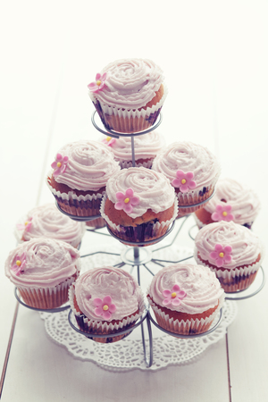 Pink cupcakes on cupcake stand on wooden background photo