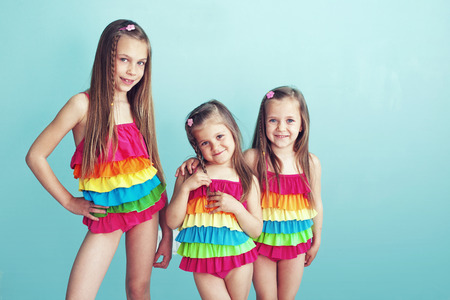 three layered: Group of children dressed in fashion swimsuits posing on aqua blue background Stock Photo