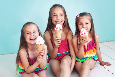 woman with ice cream: Group of children dressed in fashion swimsuits posing on aqua blue background Stock Photo