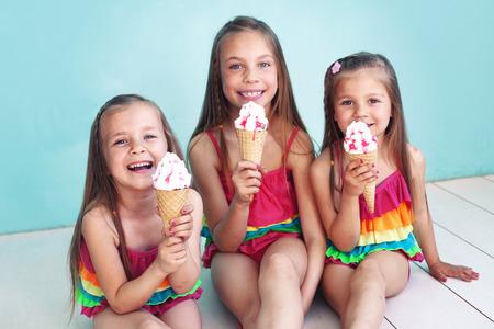 comiendo helado: Grupo de niños vestidos con trajes de baño de moda que presenta en fondo azul aqua
