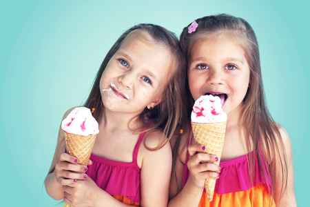 over eating: Portrait of 5 years old kid girls eating tasty ice cream over blue Stock Photo