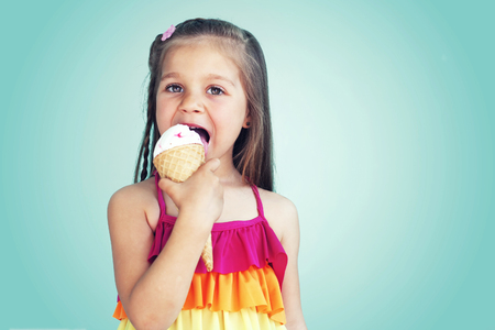 Portrait of 5 years old kid girl eating tasty ice cream over blue photo