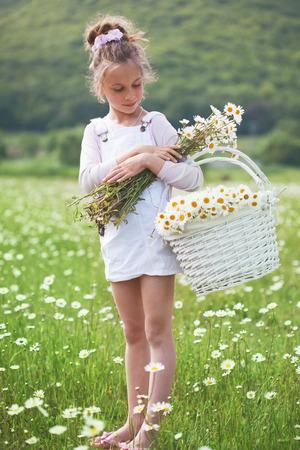 7 years old child having fun in flower field photo