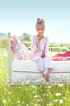 7 years old child resting on comfortable bed in spring field photo