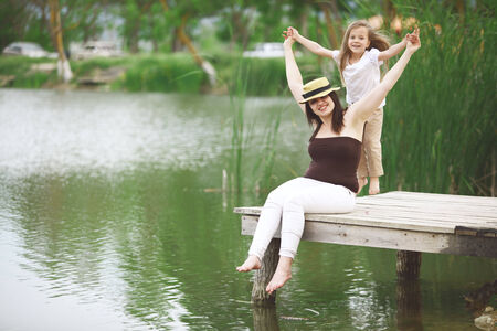 Happy young family with kids heaving fun near pond photo