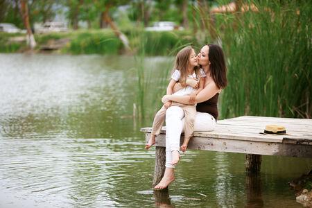 heaving: Happy young family with kids heaving fun near pond Stock Photo
