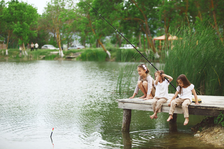 children pond: Tree children fishing in pond in summer Stock Photo
