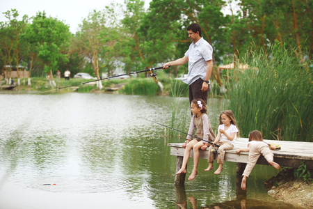 Young happy family with kids fishing in pond in summer Фото со стока - 28552424