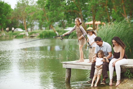 children pond: Young happy family with kids fishing in pond in summer Stock Photo