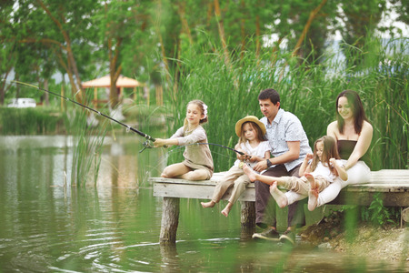 Young happy family with kids fishing in pond in summer Stock Photo