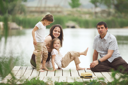 Young family with children resting near pond photo