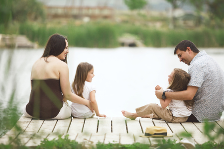children pond: Young family with children resting near pond