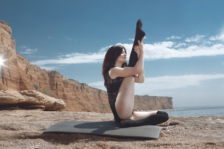 young gymnast: Young beautiful gymnast posing on the summer beach