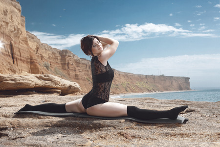 Young beautiful gymnast posing on the summer beach photo
