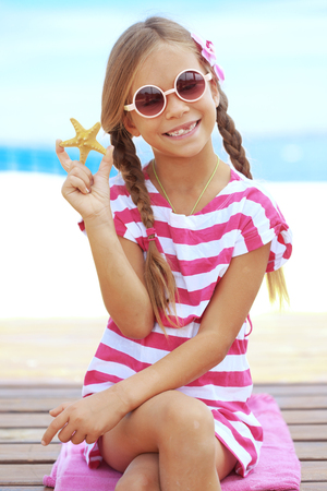 Child holding seashell on the summer beach photo