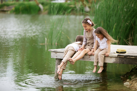 children pond: Children resting near pond in summer