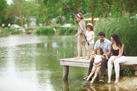 Young happy family with kids fishing in pond in summer Stok Fotoğraf