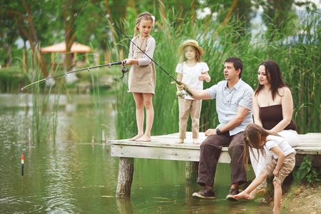 Young happy family with kids fishing in pond in summer photo