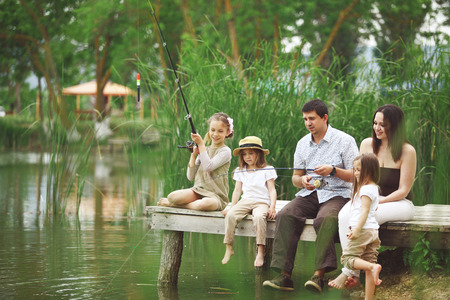 resting rod fishing: Young happy family with kids fishing in pond in summer Stock Photo