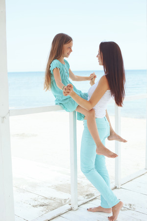 Mother with her 7 years old daughter having fun at beach in summer photo