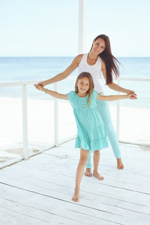 preteens beach: Mother with her 7 years old daughter having fun at beach in summer