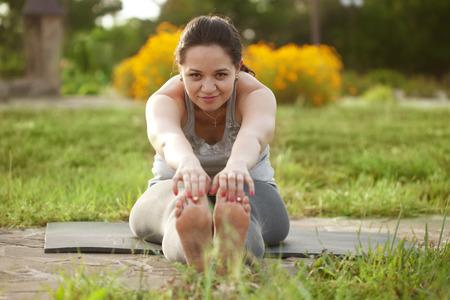 屋外ヨガの練習を行う若い女性 写真素材