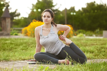 Young woman doing yoga exercise outdoors photo