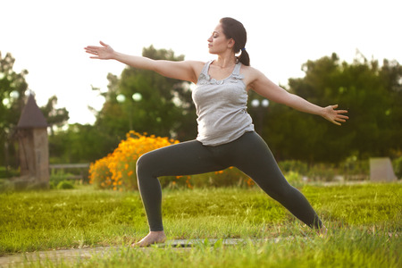 to size: Young woman doing yoga exercise outdoors