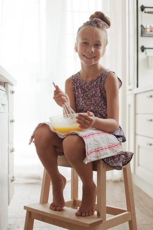 7 years old school girl cooking on the vintage kitchen, casual lifestyle photo series Stock Photo - 29005478