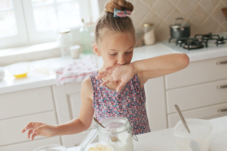 7 years old school girl cooking at the kitchen, casual lifestyle photo series Stock Photo - 29005481
