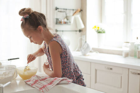 7 years old: 7 years old school girl cooking at the kitchen, casual lifestyle photo series