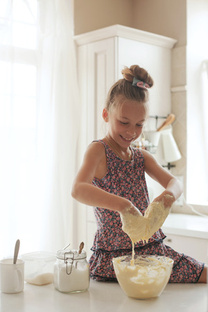 7 years old school girl cooking at the kitchen, casual lifestyle photo series Stock Photo - 29005538