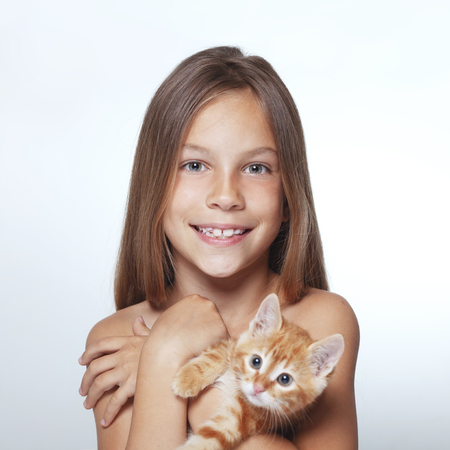 Portrait of 7 years old kid girl holding small kitten Stock Photo - 29289667