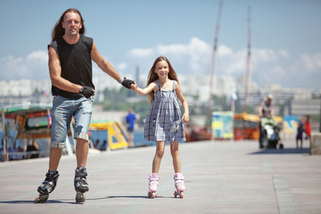 Father with his small daughter rollerskating in city street photo