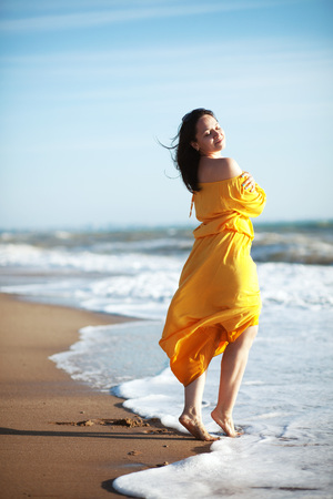casual dress: Young happy woman wearing yellow dress walking at the coastline