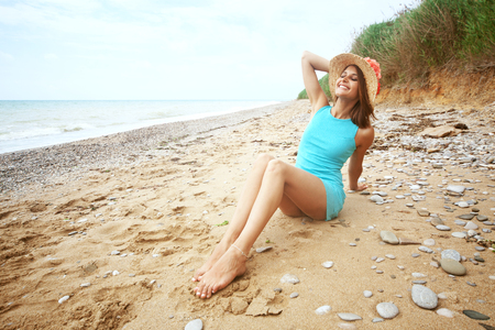 Portrait of beautiful girl with long legs posing on the beach photo