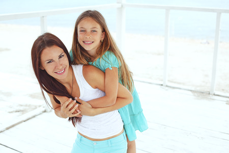 eight year old: Mother with her 7 years old daughter having fun at beach in summer