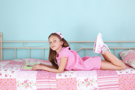 beautiful preteen girl: Portrait of 7 years old school girl reading a book on pink bed in her nursery at home