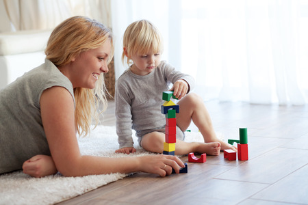 Mother with a child playing with wooden blocks at home