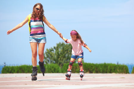 rollerblading: Young mother with her 5 years old daughter rollerskating in park Stock Photo
