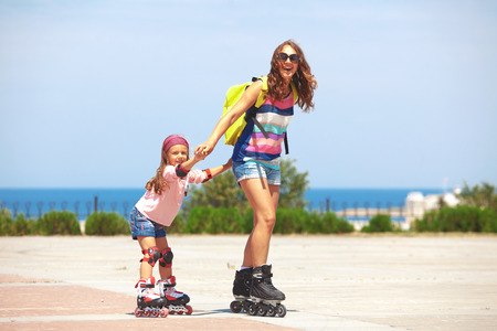 Young mother with her 5 years old daughter rollerskating in park photo