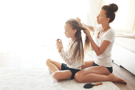 Mother hairdressing her preteen daughter at home photo