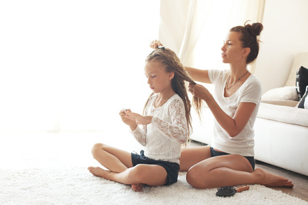 woman sitting floor: Mother hairdressing her preteen daughter at home