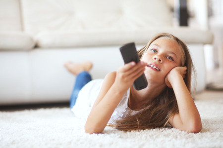 8 years old child watching tv laying down on a white carpet at home alone photo