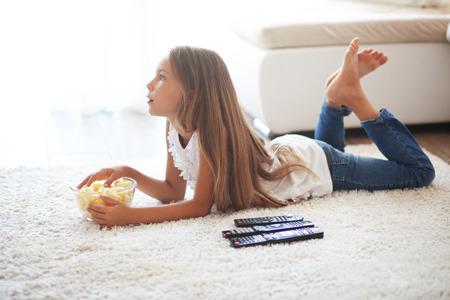 팔년 오래된 아이 혼자 집에 흰색 카펫에 누워 TV를 시청