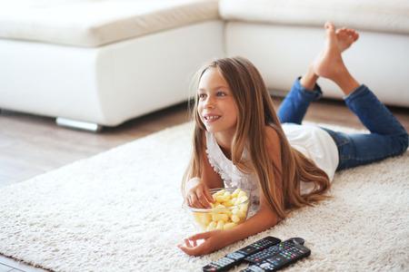 8 jaar oude kind tv kijken vaststelling op een wit tapijt alleen thuis Stockfoto