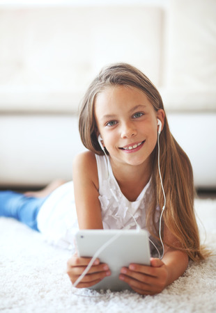 Pre teen girl playing on tablet pc laying down on a white carpet at home Stock Photo - 30381393