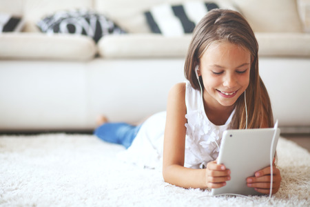 Pre teen girl playing on tablet pc laying down on a white carpet at home photo