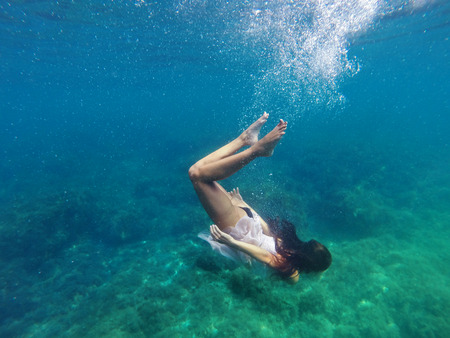 Underwater photo of a human diving in blue sea water photo